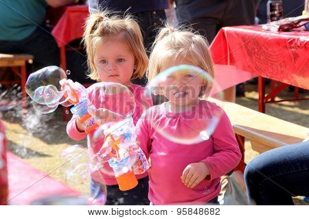 Small Sisters Playing With Bubbles At Festival South Africa
