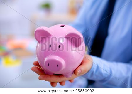 Businessman holding piggy box ,standing in office