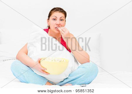 Brunette Attentively Watching Television And Eating Popcorn