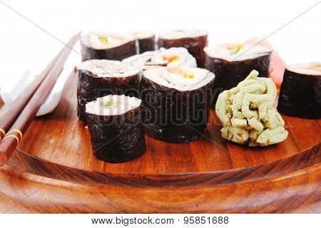 Japanese Cuisine : Sushi Maki Roll with Salmon and tuna inside . on wooden plate with wasabi and ginger isolated over white background