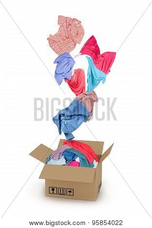 Clothes Falling Into The Cardboard Box On White