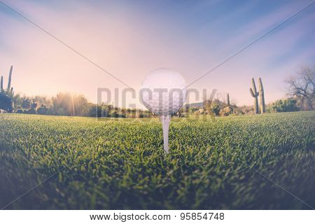 Super wide angle view of golf ball on tee with desert fairway and stunning Arizona sunset in background