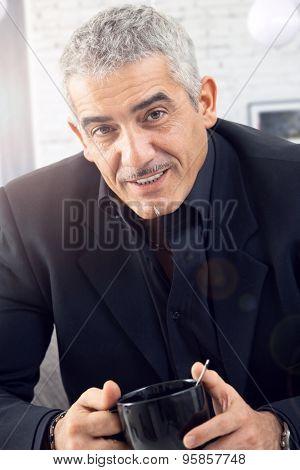 Portrait of senior businessman drinking tea, looking at camera.