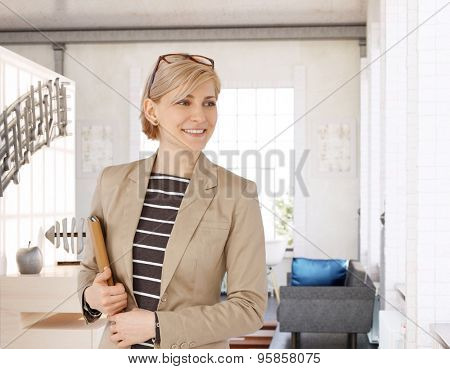 Happy businesswoman holding tablet computer, smiling, looking away.