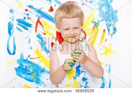 Little messy kid painting with paintbrush picture on easel. Education. Creativity. School. Preschool