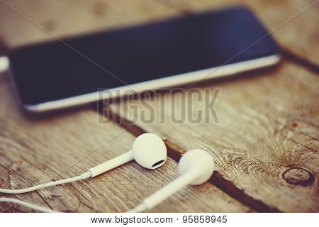 Cell Phone And Headphones Lay On An Old Wooden Table