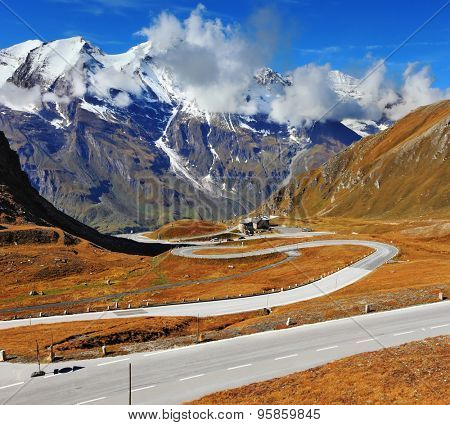 The well-known picturesque specific road in the Austrian Alps - Grossgloknershtrasse. Idealnoye Highway curls highly in mountains. The highest mountain tops are covered with fresh snow