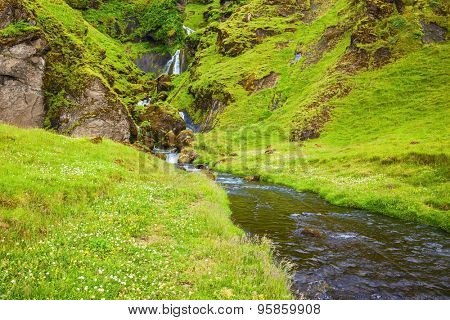 July in Iceland. Picturesque cascade step falls. Basalt mountains overgrown with a green grass and moss