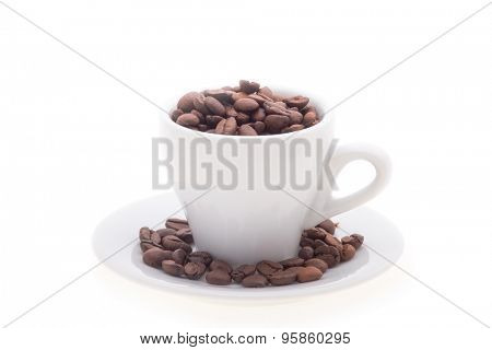 coffee beans in a white cup and saucer. Isolated on white background