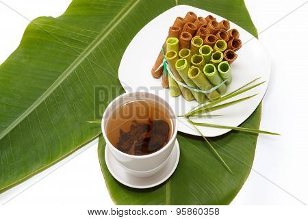 A Bunch Of Colorful Waffle Rolls On A White Plate And A Leaf With A Cup Of Tea