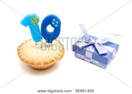 Cupcake With Ten Years Birthday Candle And Gift On White