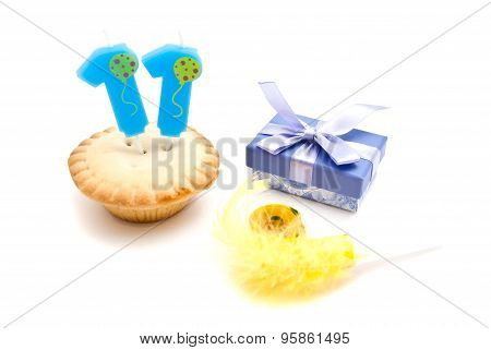 Cupcake With Eleven Years Birthday Candle, Gift And Whistle On White