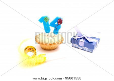 Cupcake With Fourteen Years Birthday Candle, Gift And Whistle On White