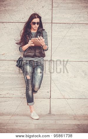 girl with tablet is walking in the downtown
