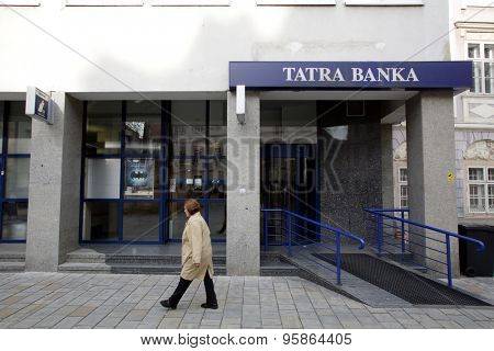 BRATISLAVA, SLOVAKIA - SATURDAY, APRIL 11, 2015:  A pedestrian walks past a branch of Tatra Banka. The bank is the first private bank in Slovakia.