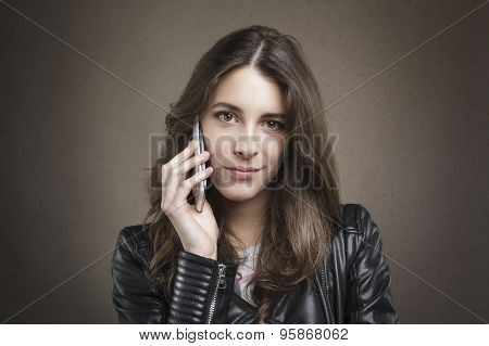 Attractive Young Girl At Phone Looking At Camera On Texture Background