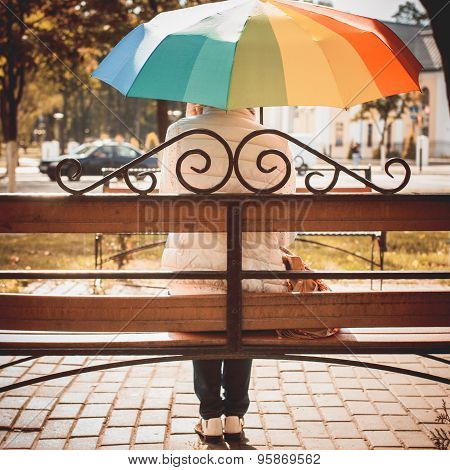 Girl Under An Umbrella Sitting On The Bench