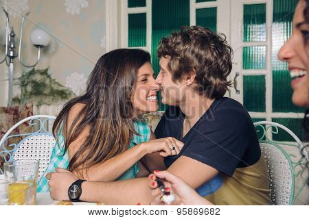 Couple in love laughing and embracing at breakfast