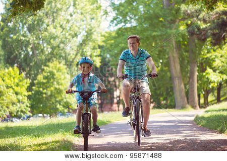 Happy Father And Son Ride On Bikes