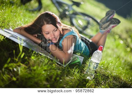 Sport girl lay on a grass with a map near the bicycle
