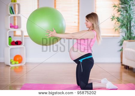 Pregnant woman holding exercise ball at home