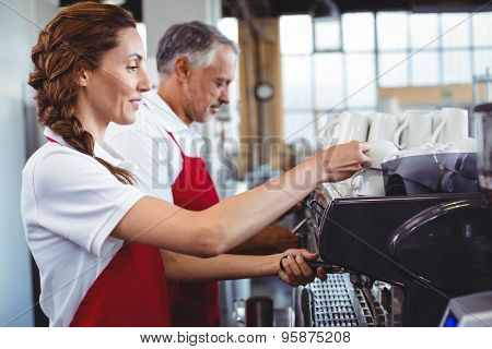 Pretty barista using the coffee machine with colleague behind at the cafe