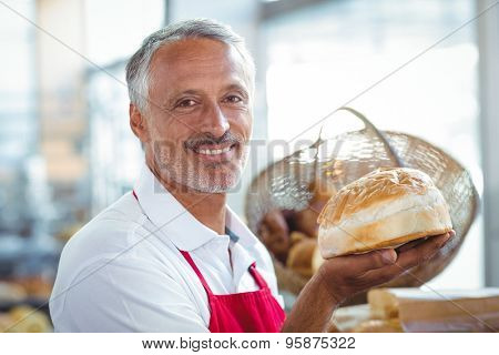 Waiter looking at camera and holding freshly baked bread in the bakery