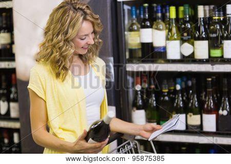 Smiling pretty blonde woman looking at notepad amd having in her hands a wine bottle in supermarket