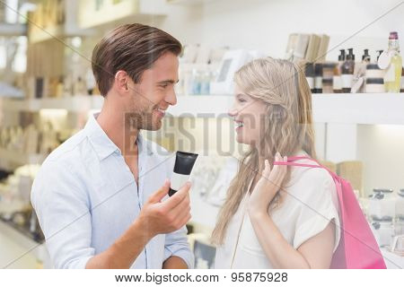 A couple testing a sample of beauty products in the mall