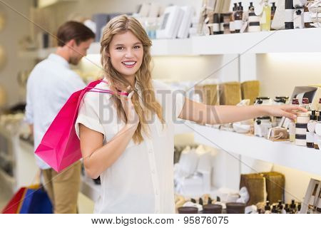 A pretty blonde woman looking at beauty product at the mall