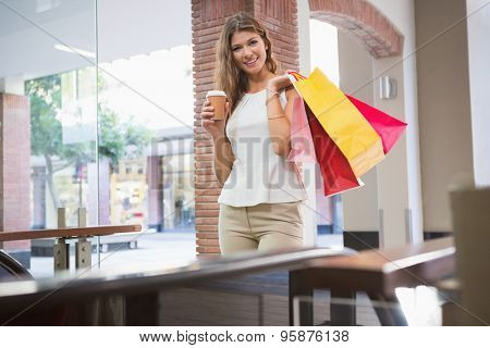 Portrait of smiling woman with shopping bags and coffee to go looking at camera at the shopping mall