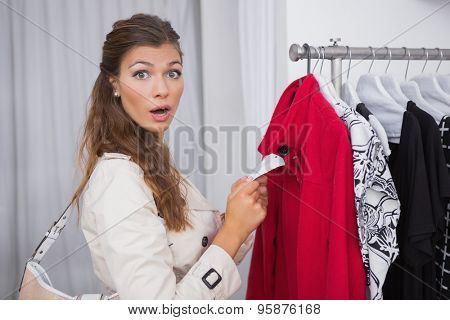 Portrait of surprised woman holding price tag and looking at camera at a boutique