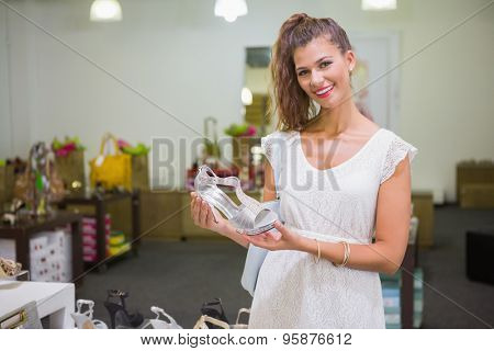 Portrait of smiling woman holding high-heeled sandal at a shoe shop