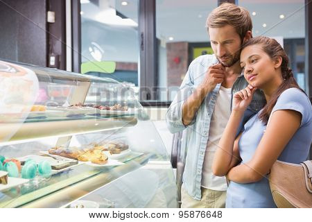 Young happy couple choosing cake in the cafe
