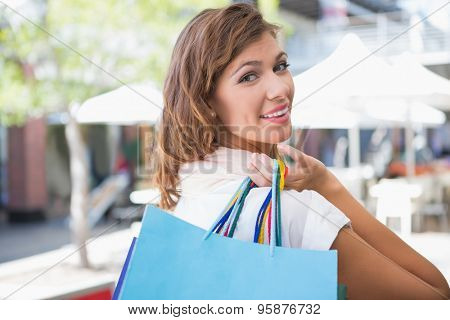Portrait of smiling woman holding shopping bag and looking over the shoulder at camera