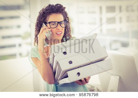 Stunned businesswoman carrying a stack of folders while on the phone
