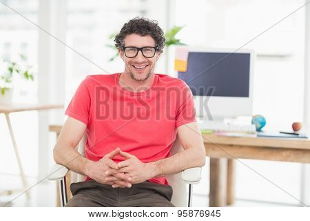 Handsome businessman sitting on a swivel chair and using his laptop in the office