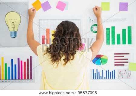 Young businesswoman facing the wall with charts in the office