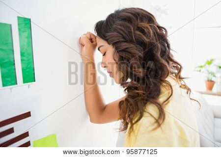 Young businesswoman leaning against the wall with the arm resting against it in the office