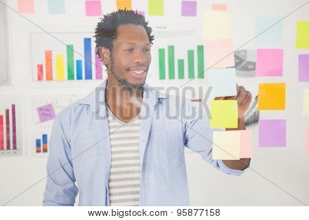 Casual businessman looking at post-it in the office