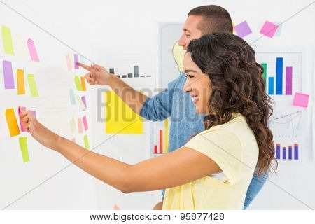 Smiling coworkers pointing sticky notes in the office