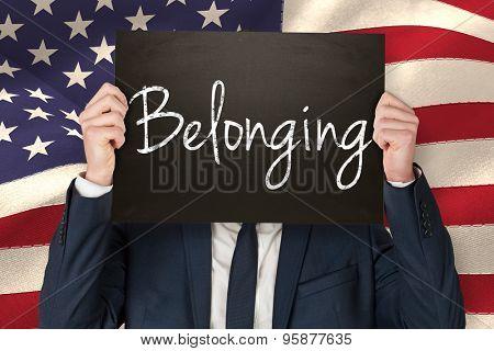 Businessman holding board against belonging