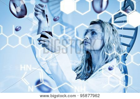 Female scientist examining blood against science graphic