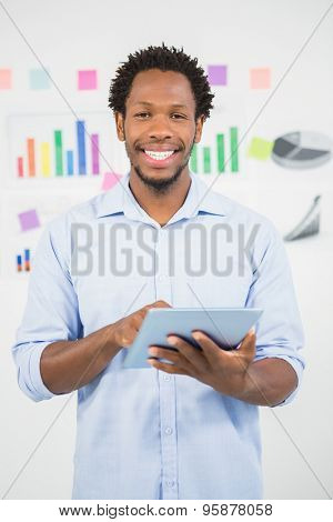Young smiling creative businessman in the office with a tablet