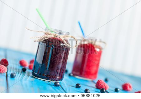 Glass mason jar with raspberry and blueberry jam. Fresh raspberries, blueberries on the blue wooden