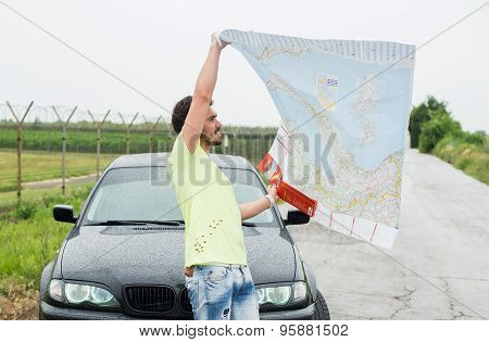Young man parked his car by the side of a road, lost and reading  map