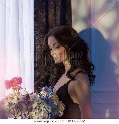 Fashion art photo of sensual lady with flowers. Home interior. Sunset