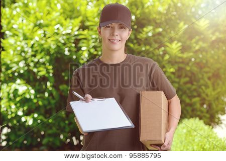 Smiling Female Courier Delivering A Parcel