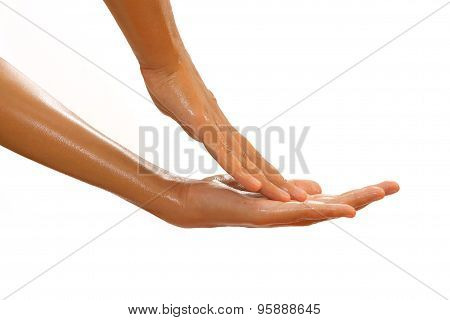Close-up Of Female Hands While Applying Oil