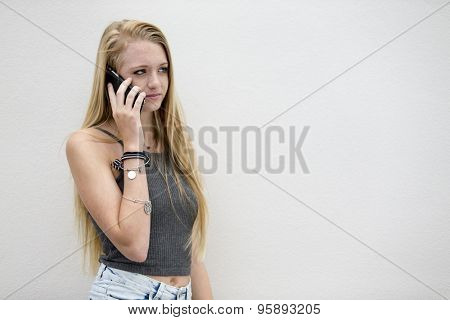 A teenage blonde model posing outdoors on a cellphone